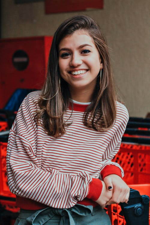 Photo of Smiling Woman in Striped Sweatshirt Standing Next to Shopping cart