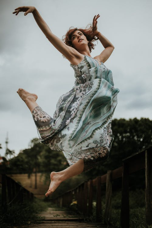 Woman Jumping Wearing Green