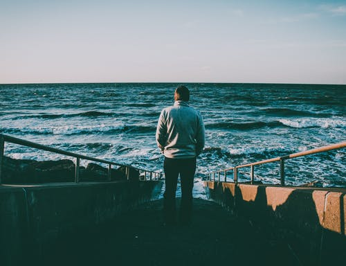 Man Walking on Stairs Near Ocean