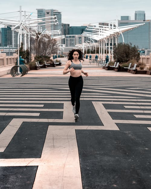 Woman In Grey Sports Bra Running On Road