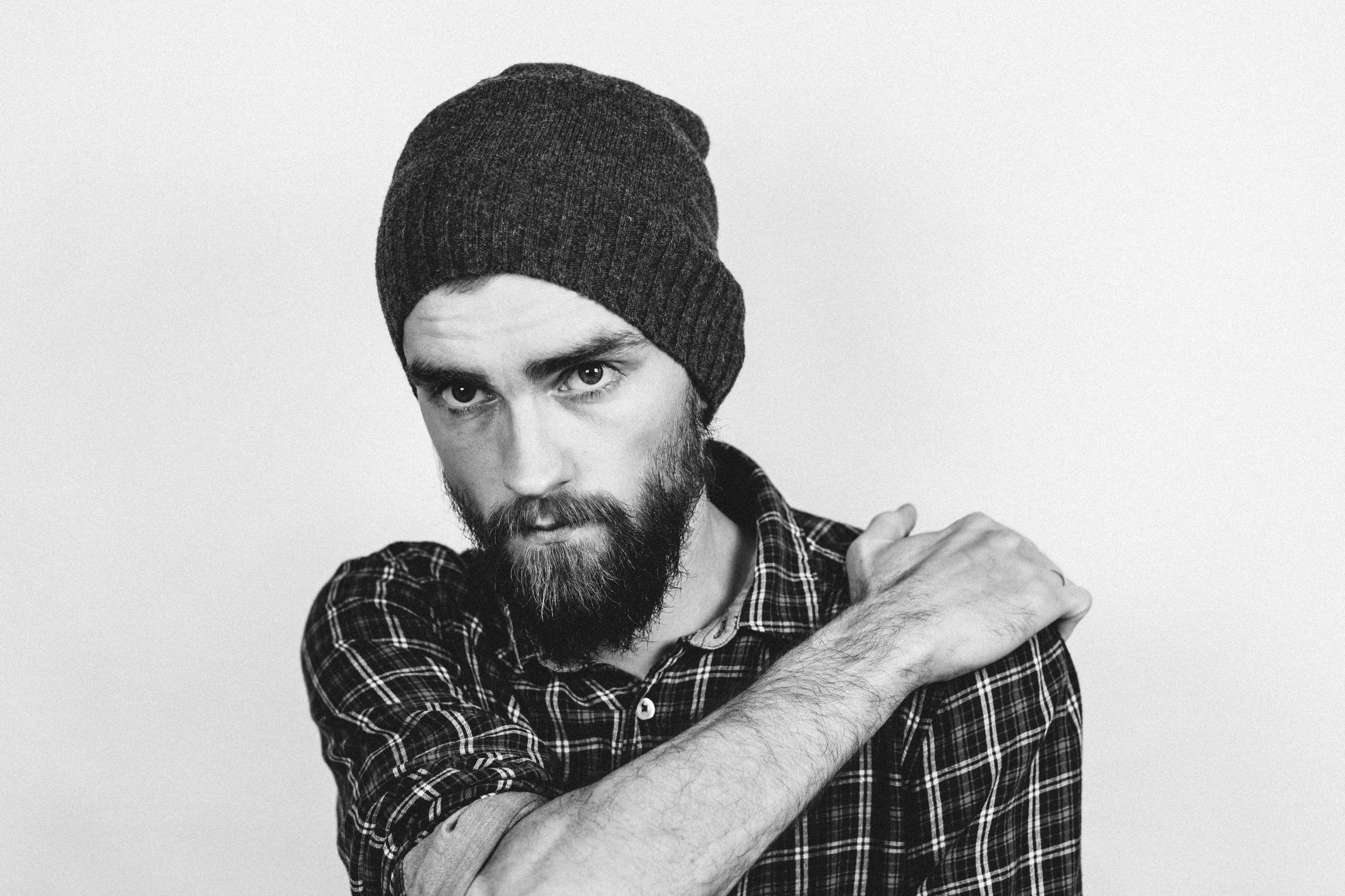 Man in Beanie Holding His Shoulder