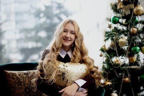 Smiling Woman Sitting Beside Christmas Tree