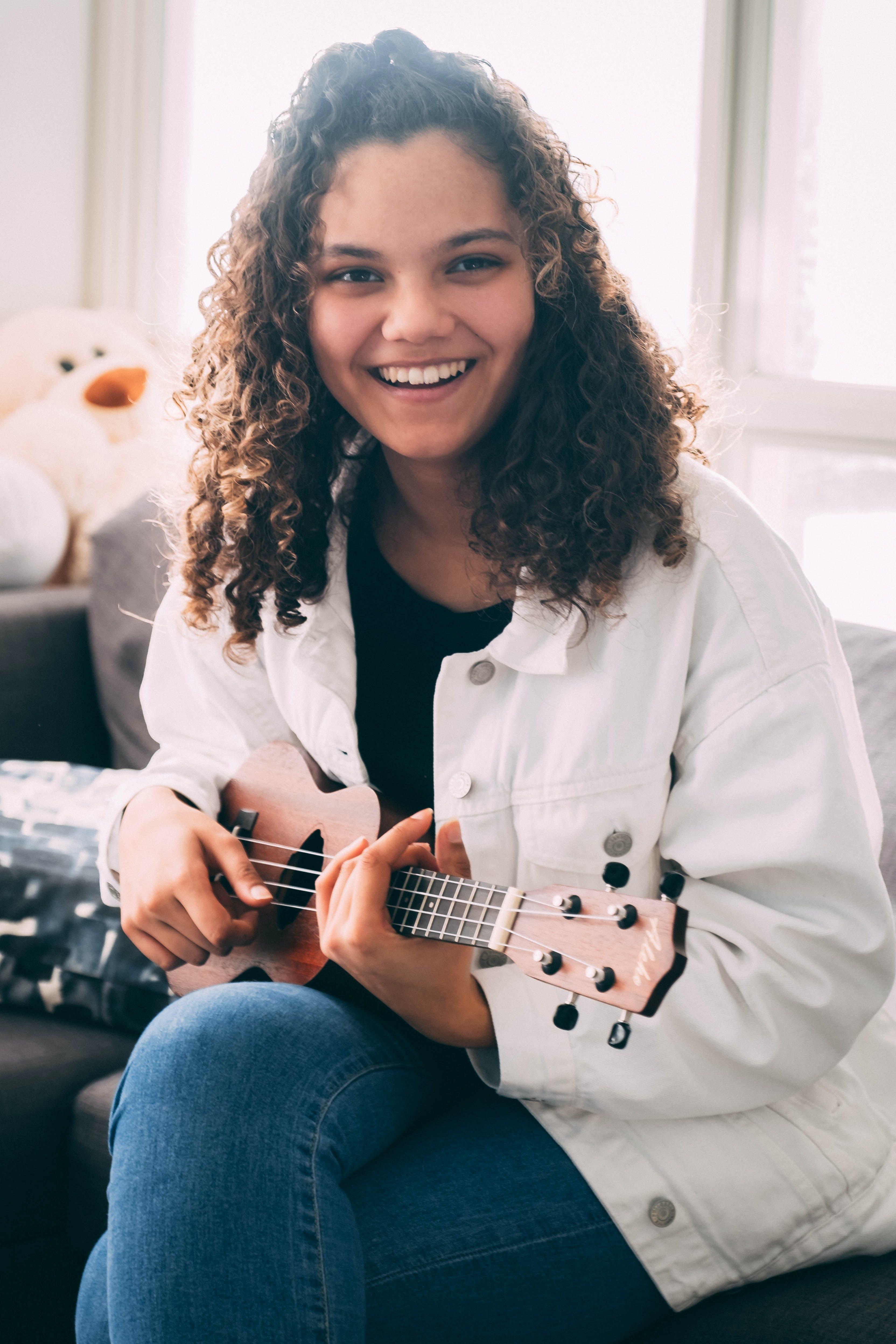 Kostenloses Stock Foto zu gitarre, haar, jeans, lachen