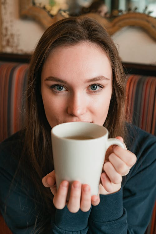 Selective Focus Photography Of Woman Holding White Ceramic Mug