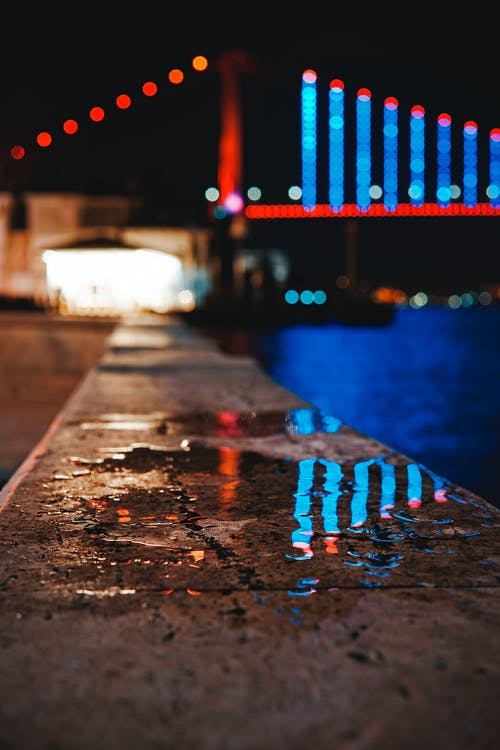 Wet Pavement Near Lighted Bridge