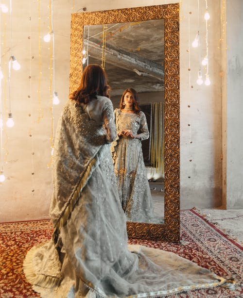 Woman In Silver Dress Standing In Front Of Mirror