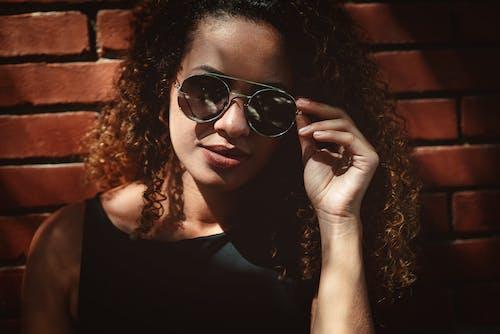 Woman Holding Sunglasses Beside Wall