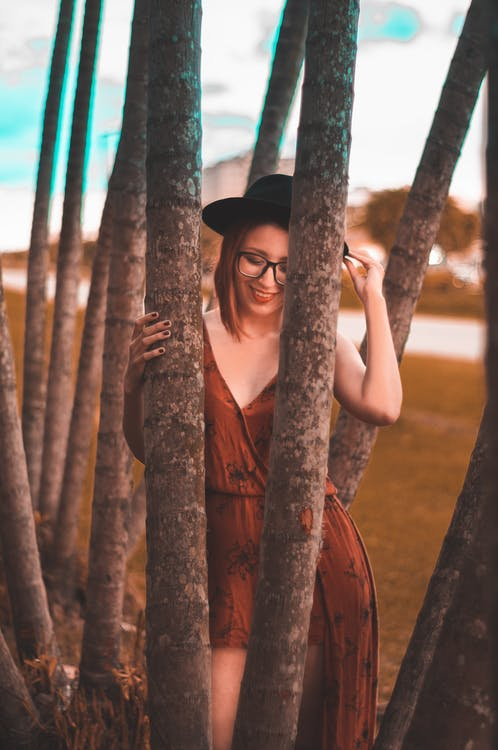 Woman Wearing Brown Dress Holding a Tree