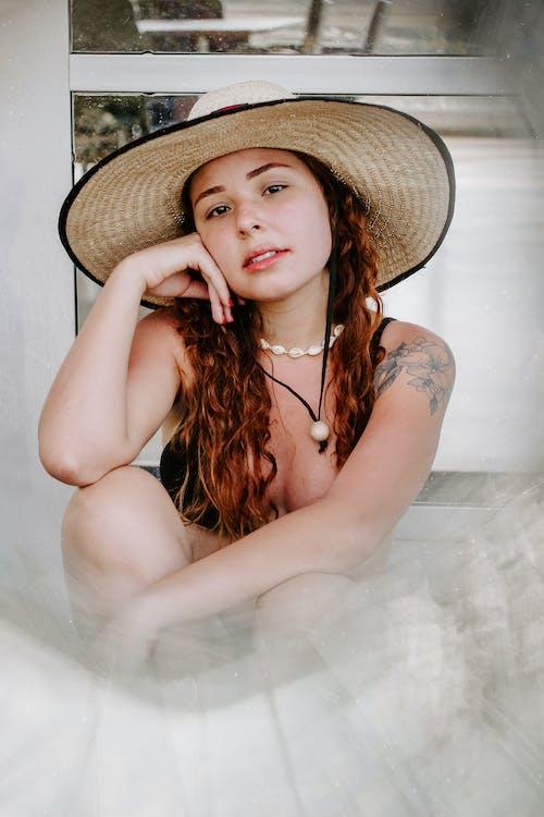 Woman in Bikini and Straw Hat Sitting on Sand