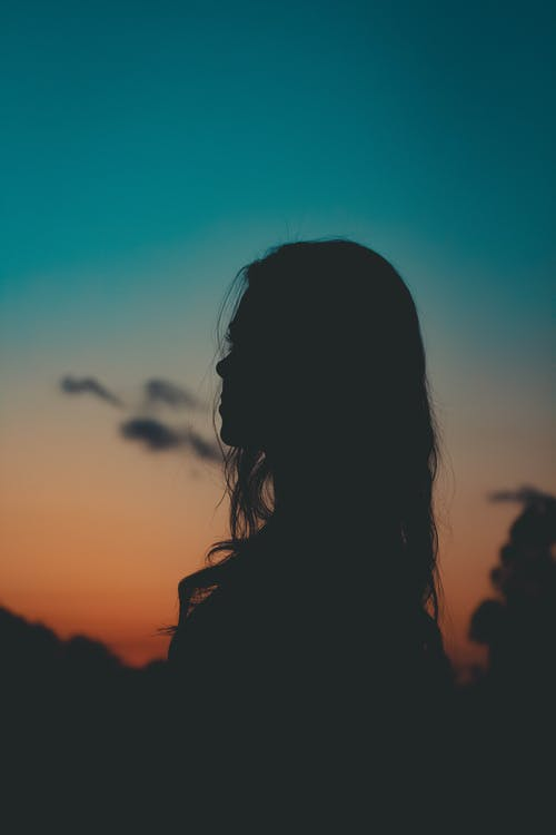 Silhouette of Woman Across Blue and Orange Sky
