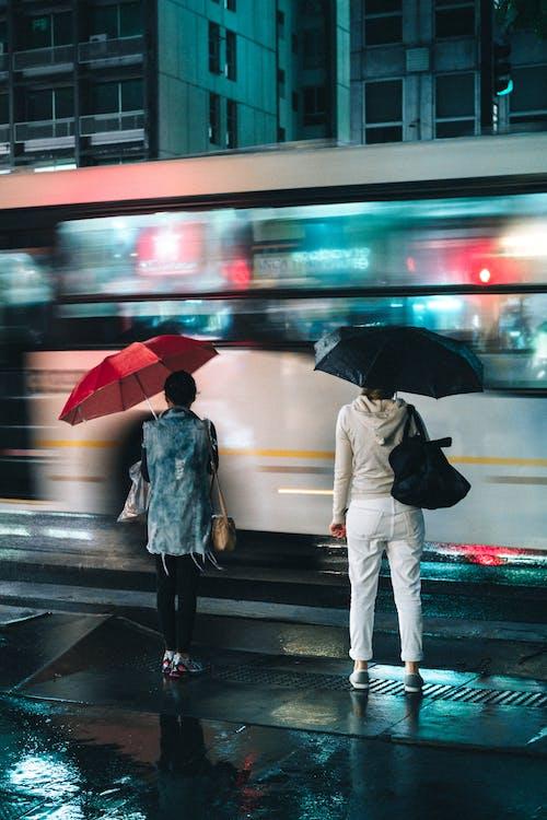 Women Standing Under Open Umbrellas Outdoors during Nighttime