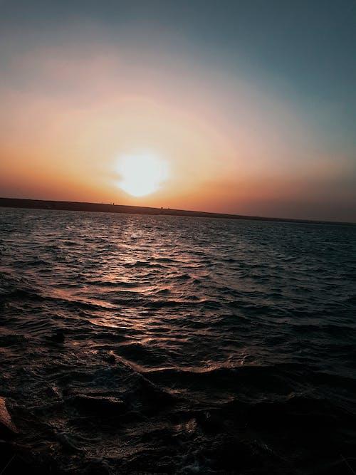 Photos gratuites de le soleil couchant sur la plage