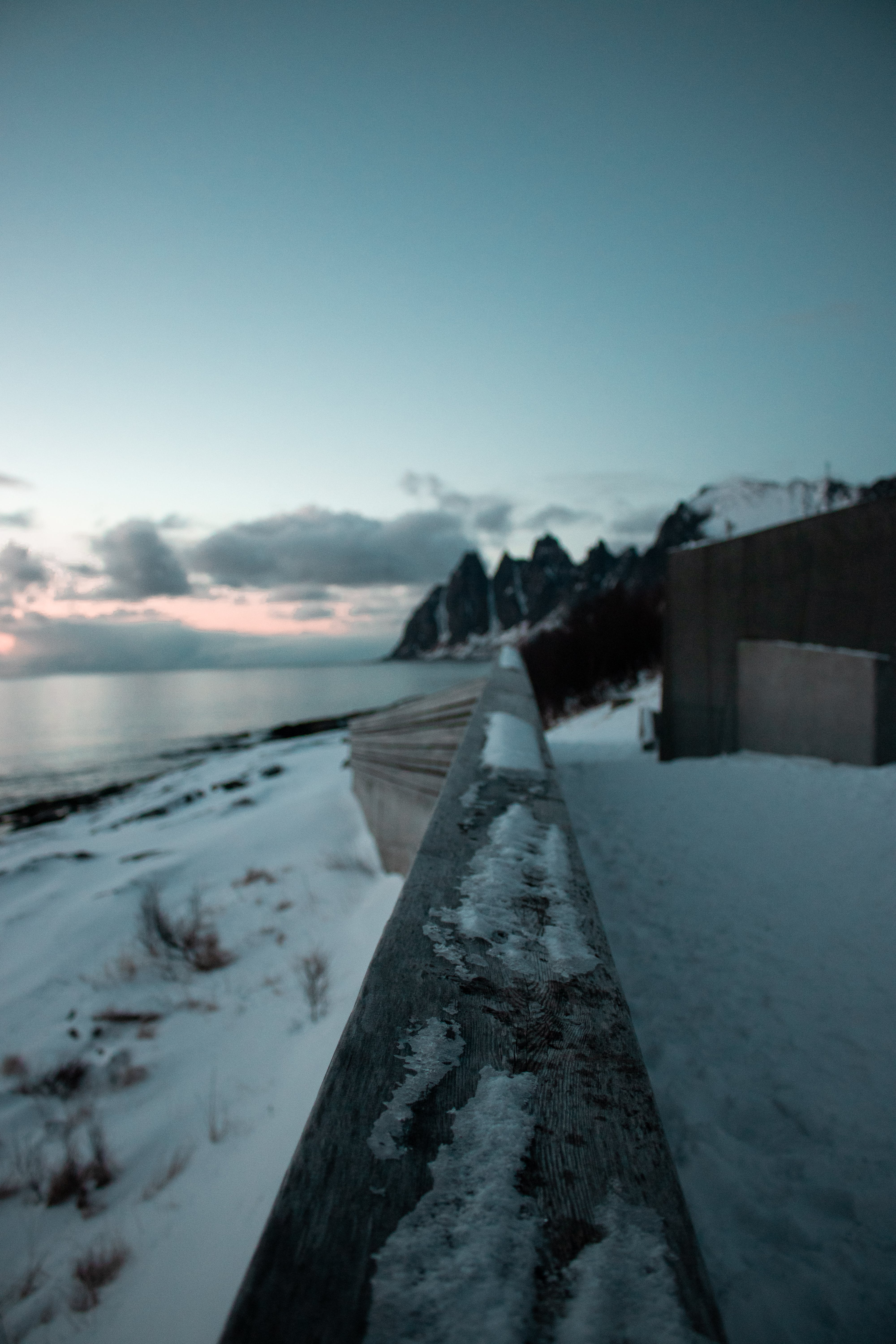 Brown and Gray Wall Surrounded by Snow Near Body of Water