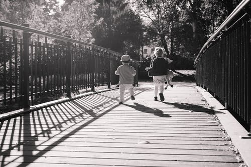 Children Running Together on Wooden Path Way Bridge