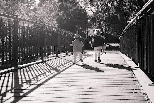 Children Running Together on Wooden Path Way Bridge