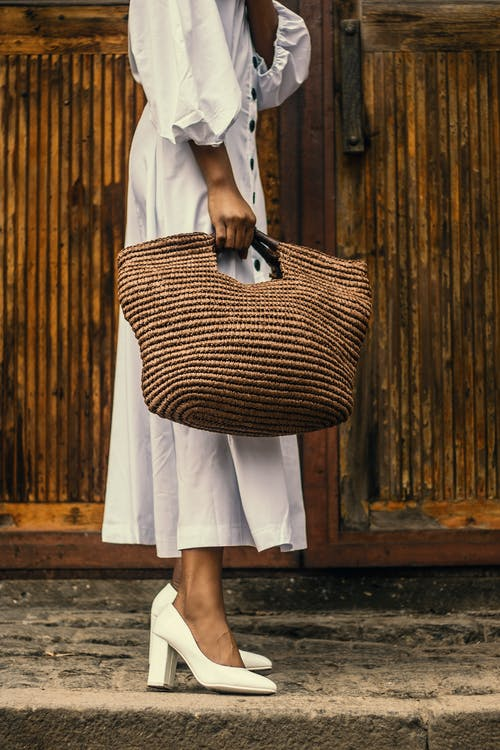 Woman Holding Brown Bag Near Brown Wooden Surfac