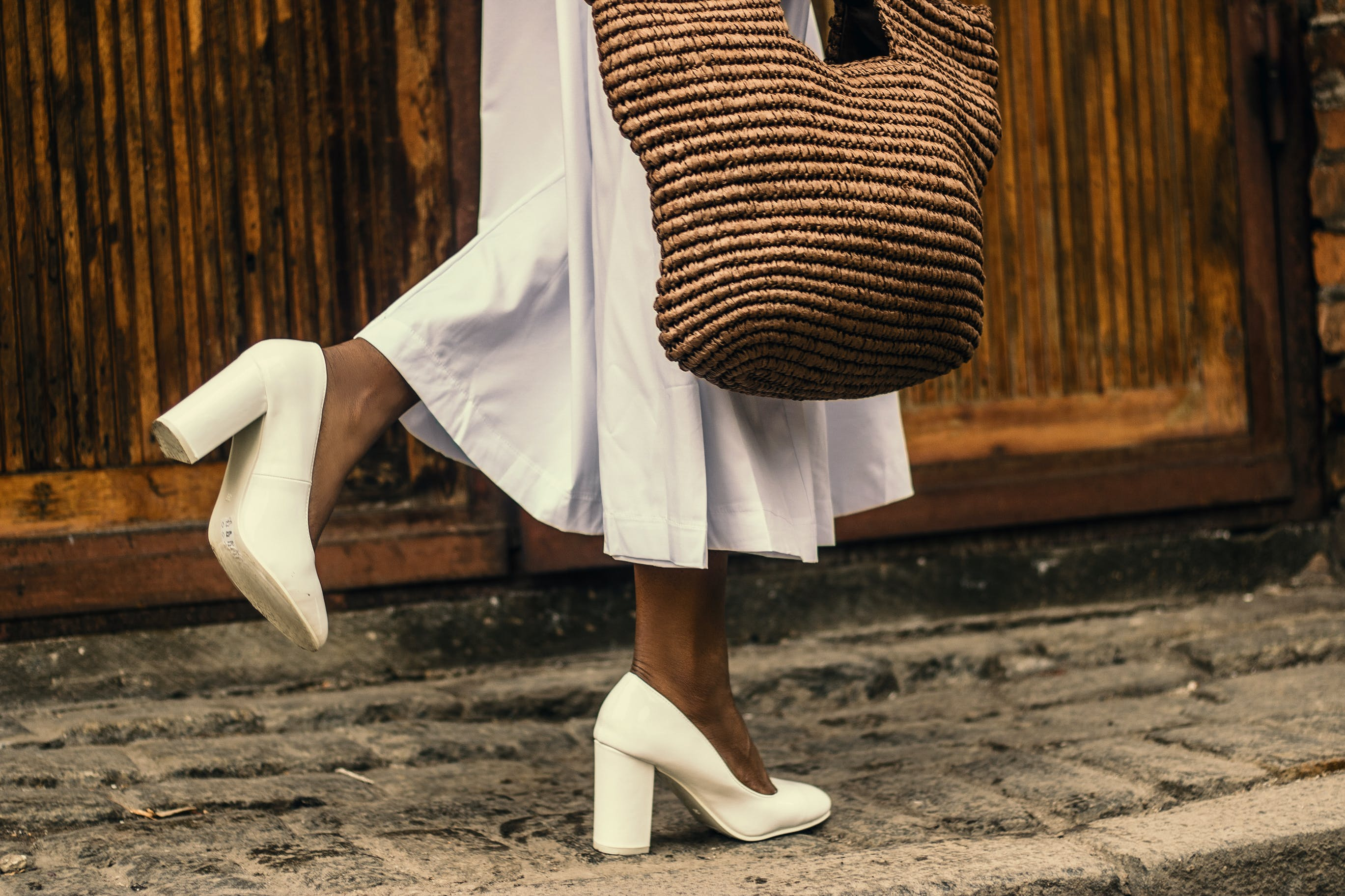 Woman Wearing White Dress and White High-heeled Shoes While Walking on Sidewalk