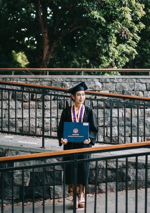 Dreamy Asian female bachelor with diploma on bridge