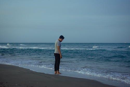 Man Wearing Gray Shirt Standing on Shore