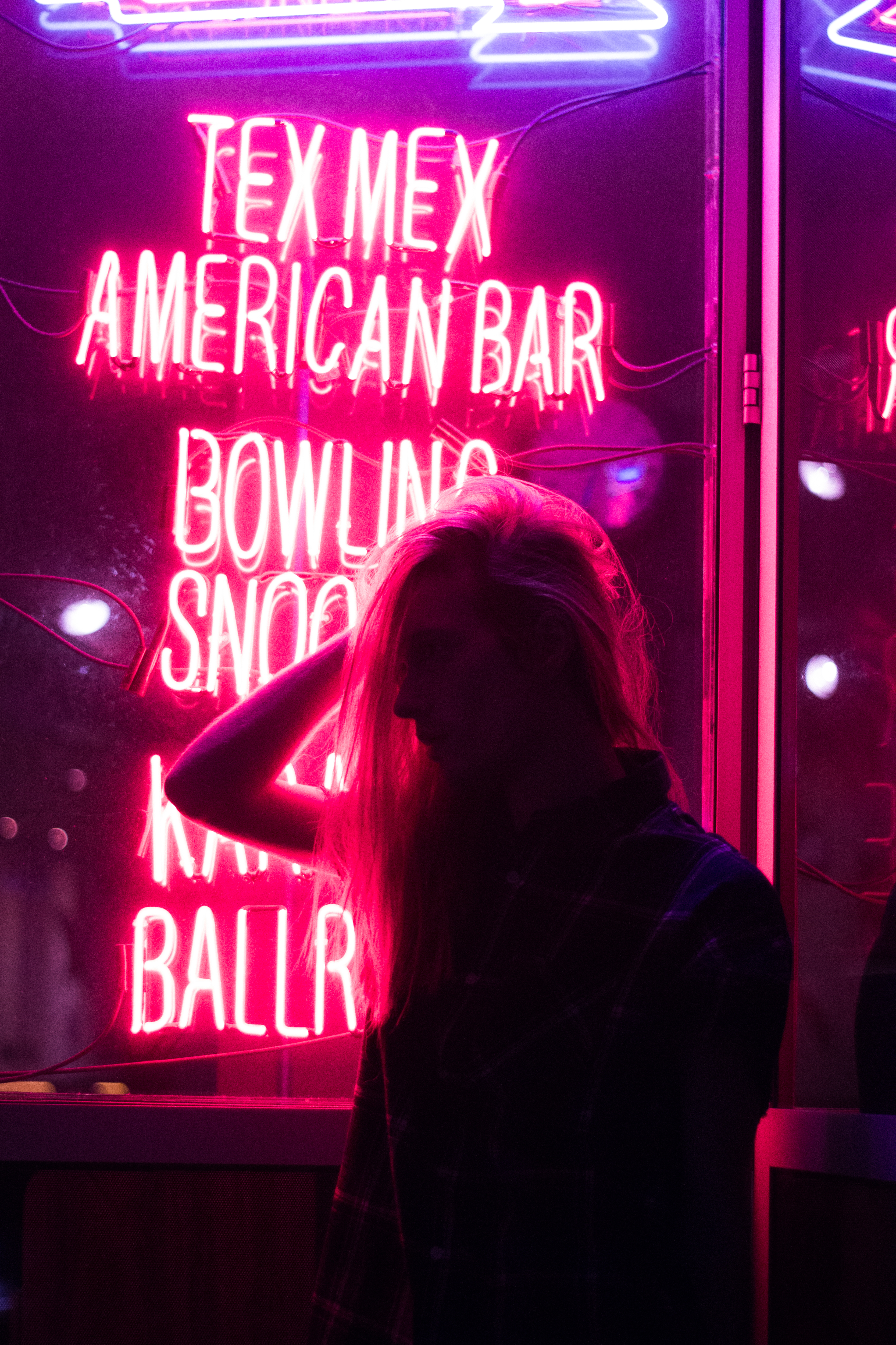 Girl Holding Her Hair Near the Neon Light Signage