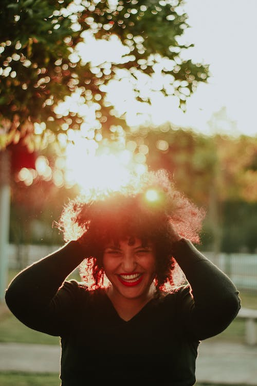 Woman Wearing Black Sweater Holding Her Hair While Smiling