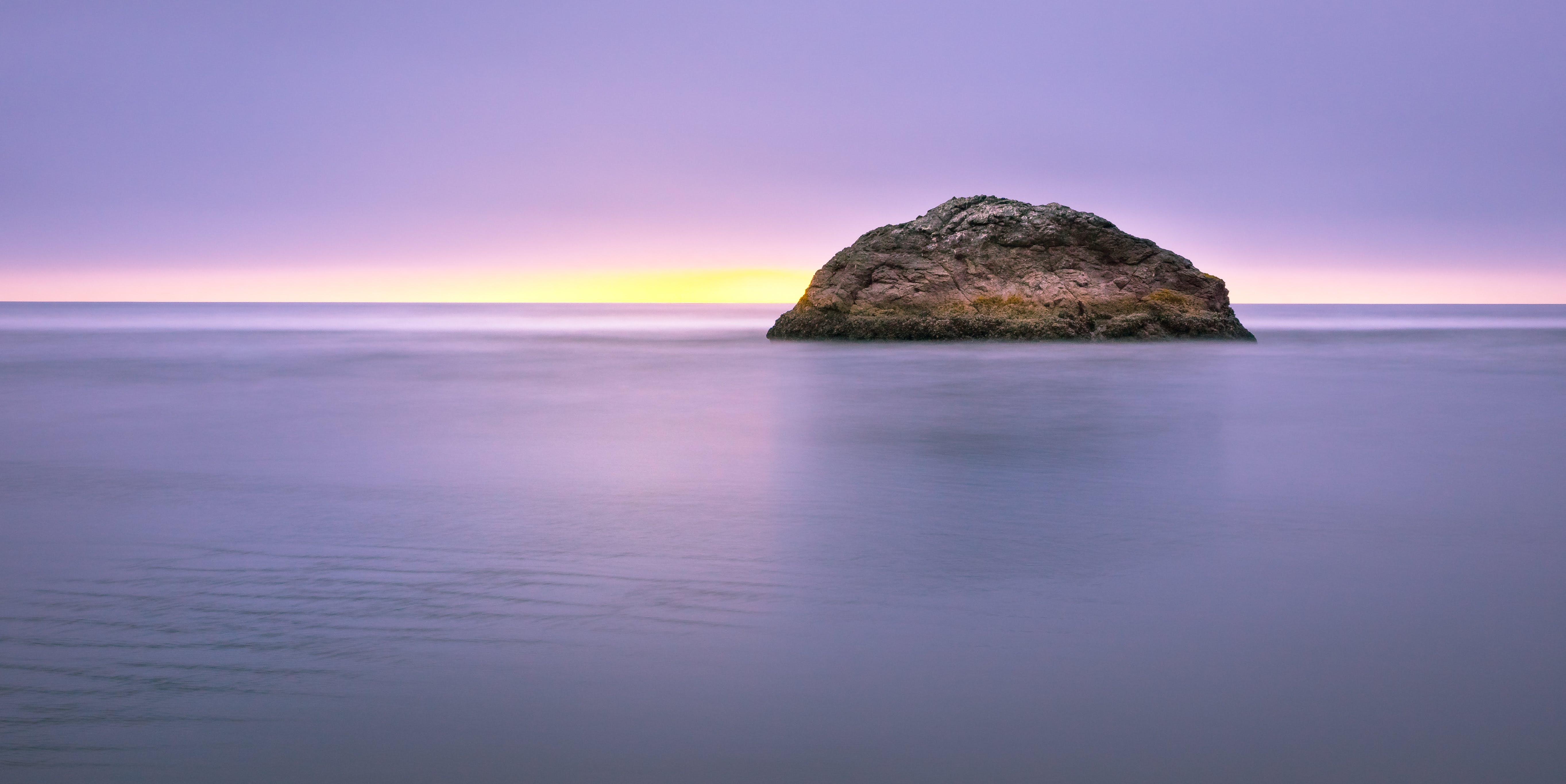 Photo of Island on Sea during Sunset