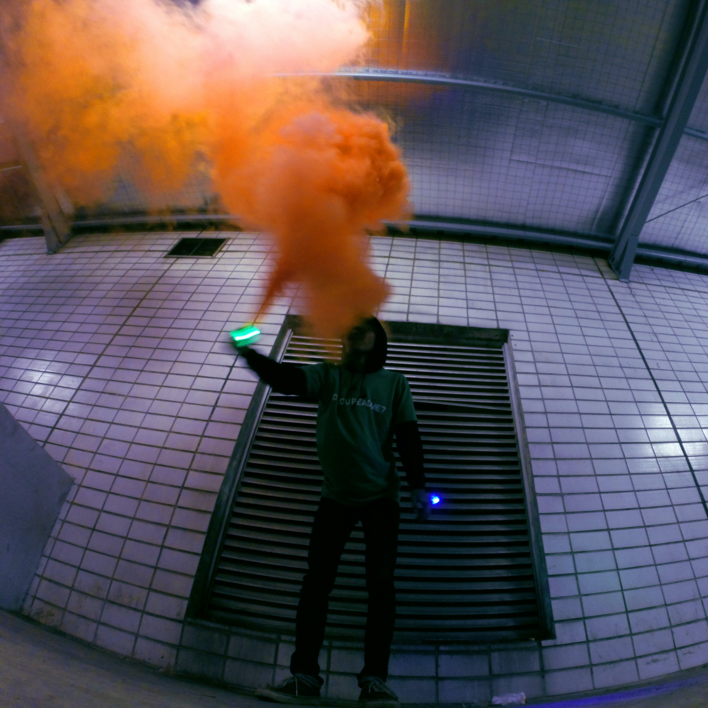 Man Holding Lighted Device over Orange Smoke