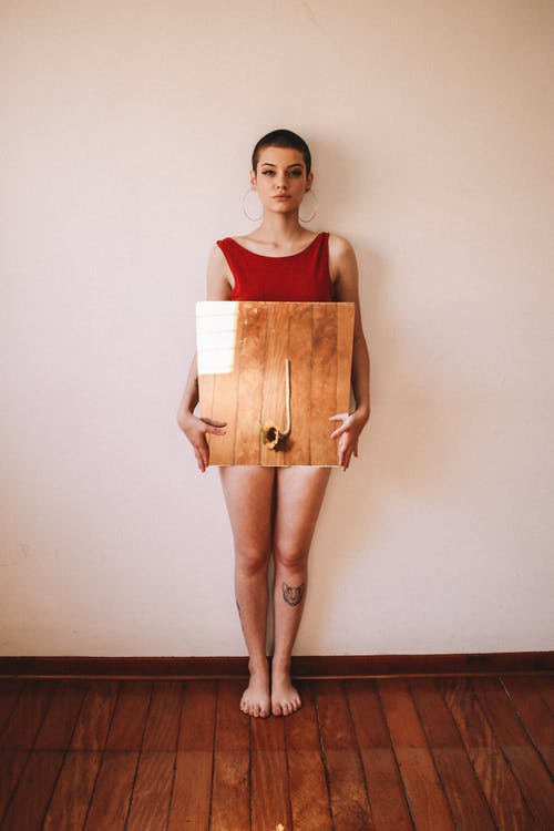 Woman Standing Against Wall Holding Brown Board