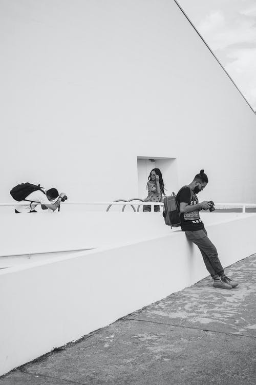 Grayscale Photo of Man Using Camera