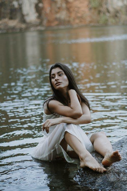 Woman Wearing White Sleeveless Dress Sitting Beside Body of Water