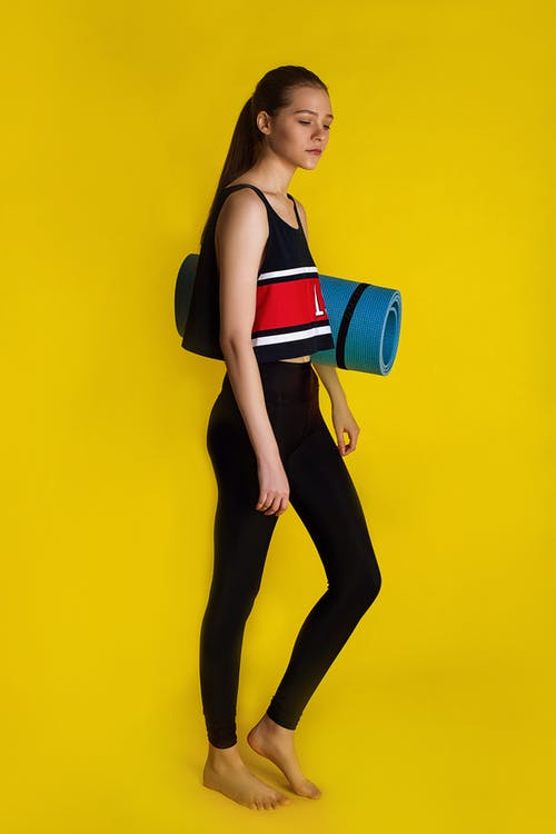 Woman in Black Tank Top and Black Leggings Holding Blue and Red Handbag