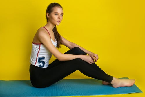 Woman in White and Red Tank Top and Black Pants Sitting on Blue Yoga Mat
