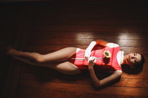Woman Wearing Red One Piece Holding Sunflower Lying on Floor