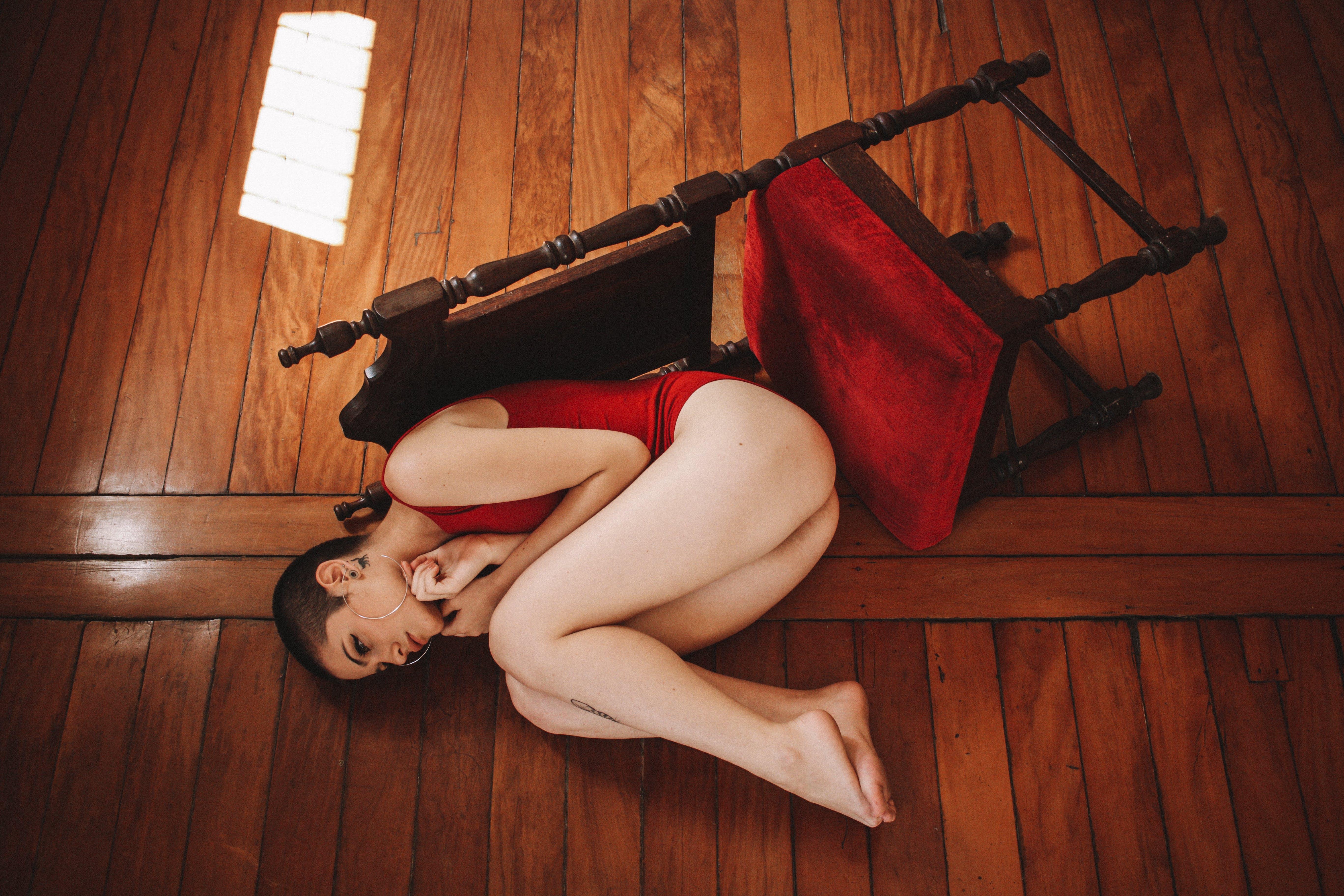 Woman Wearing Red Monokini Beside Brown Wooden Surface