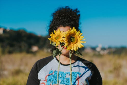 Woman Covering Her Face With Sunflowers