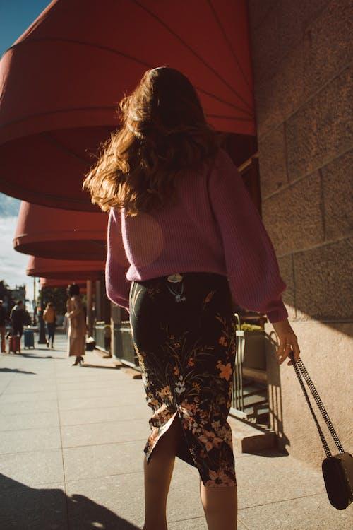 Trendy woman walking in sunny street