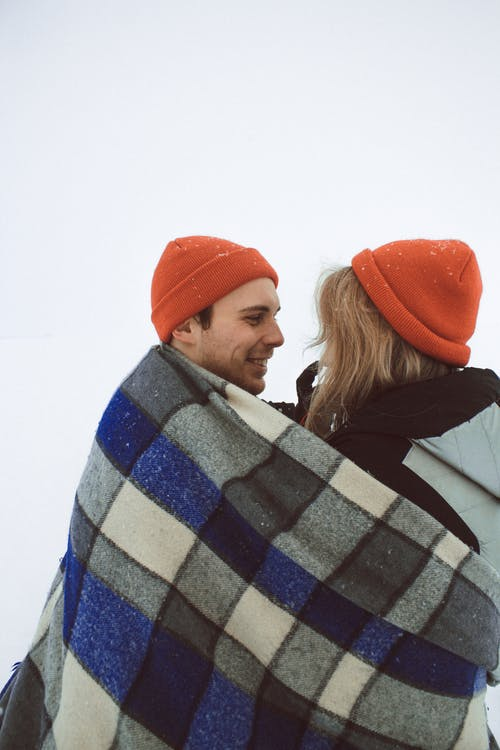 Side view of young man and woman in love in orange knitted hats embracing and looking at each other wrapped in woolen plaid on snowy slope
