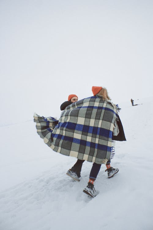 Young couple with warm blanket on shoulders walking on snow