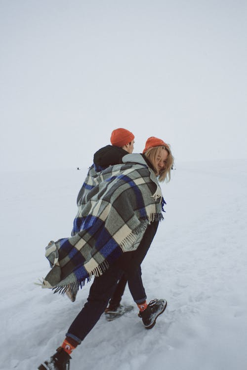 Couple walking on snow with warm plaid on shoulders