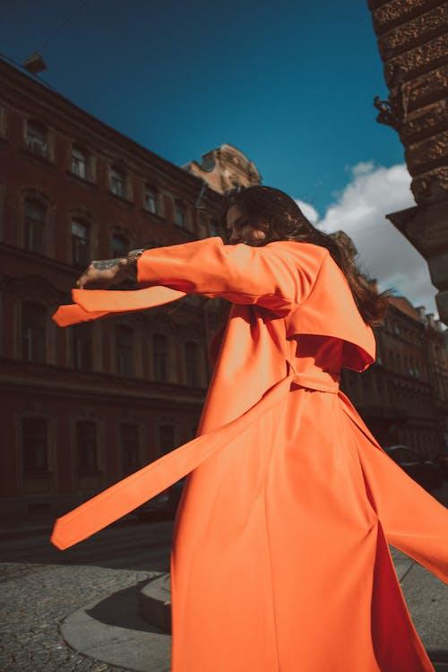 Young woman in trendy orange coat having fun in street