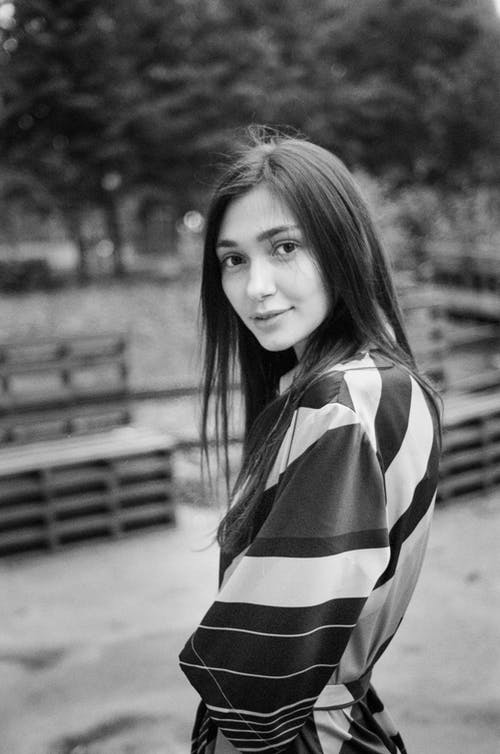 Black and white of casual brunette in striped dress looking kindly at camera standing against benches in park