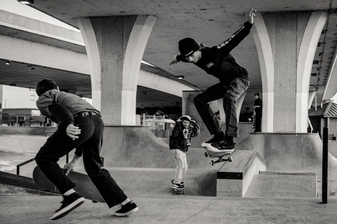 Monochrome Photo of Men Skateboarding
