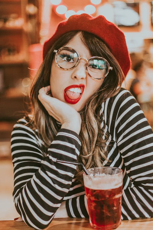 Selective Focus Photo of Woman in Black and White Striped Long-sleeved Shirt, Eyeglasses, and Red Hat Posing Next to Beverage With Her Tongue Out