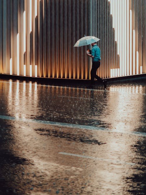Photo of Man Holding Umbrella Walking Beside Building While its Raining