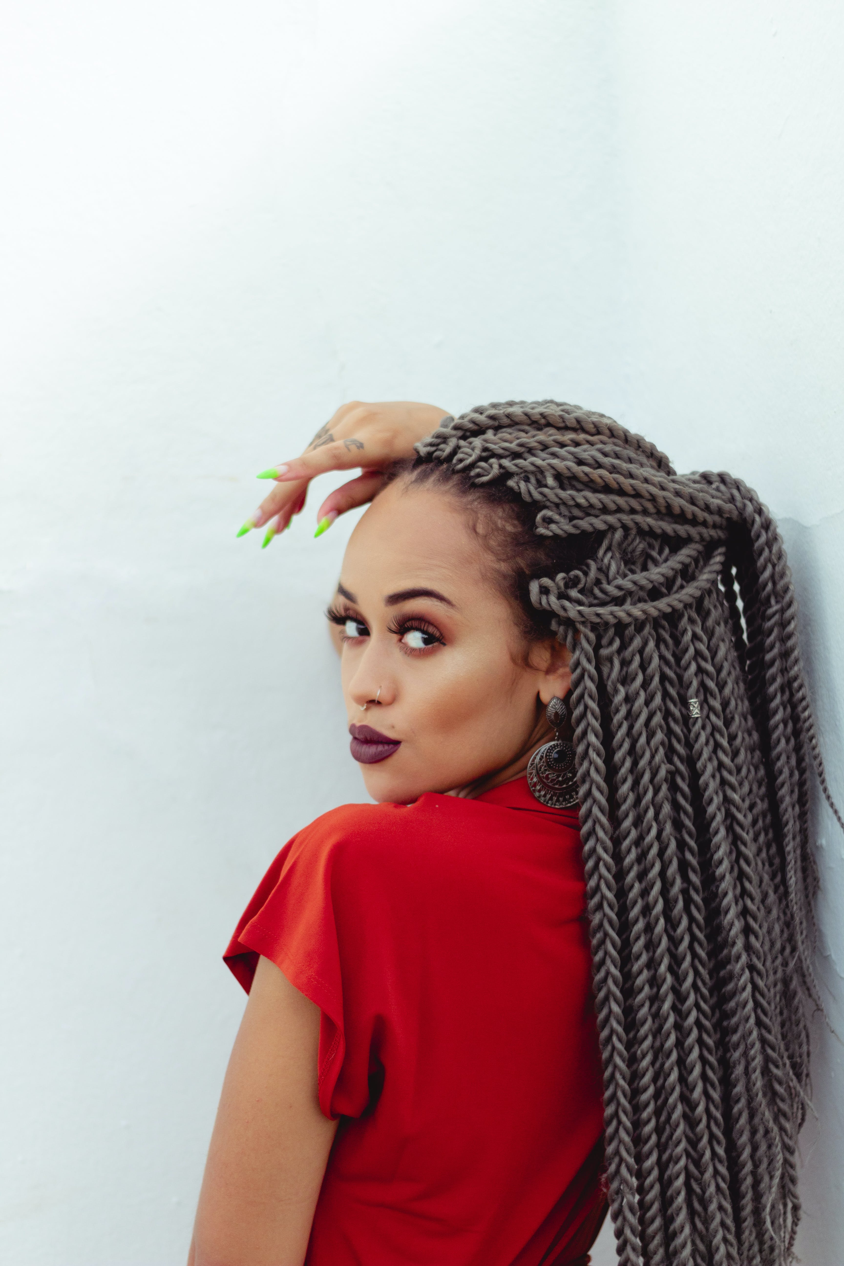 Woman In Red Top With Braided Hair Leaning On White Wall