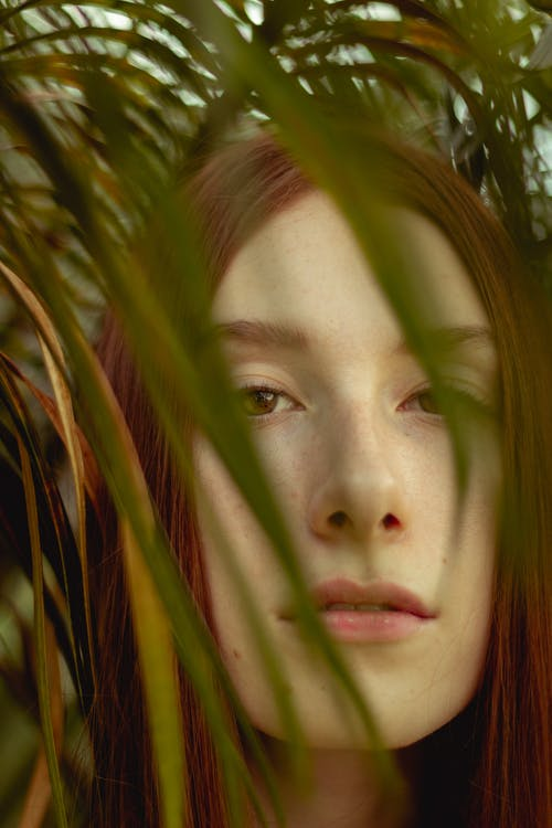 Close-Up Photo of Woman's Face Near Leaves