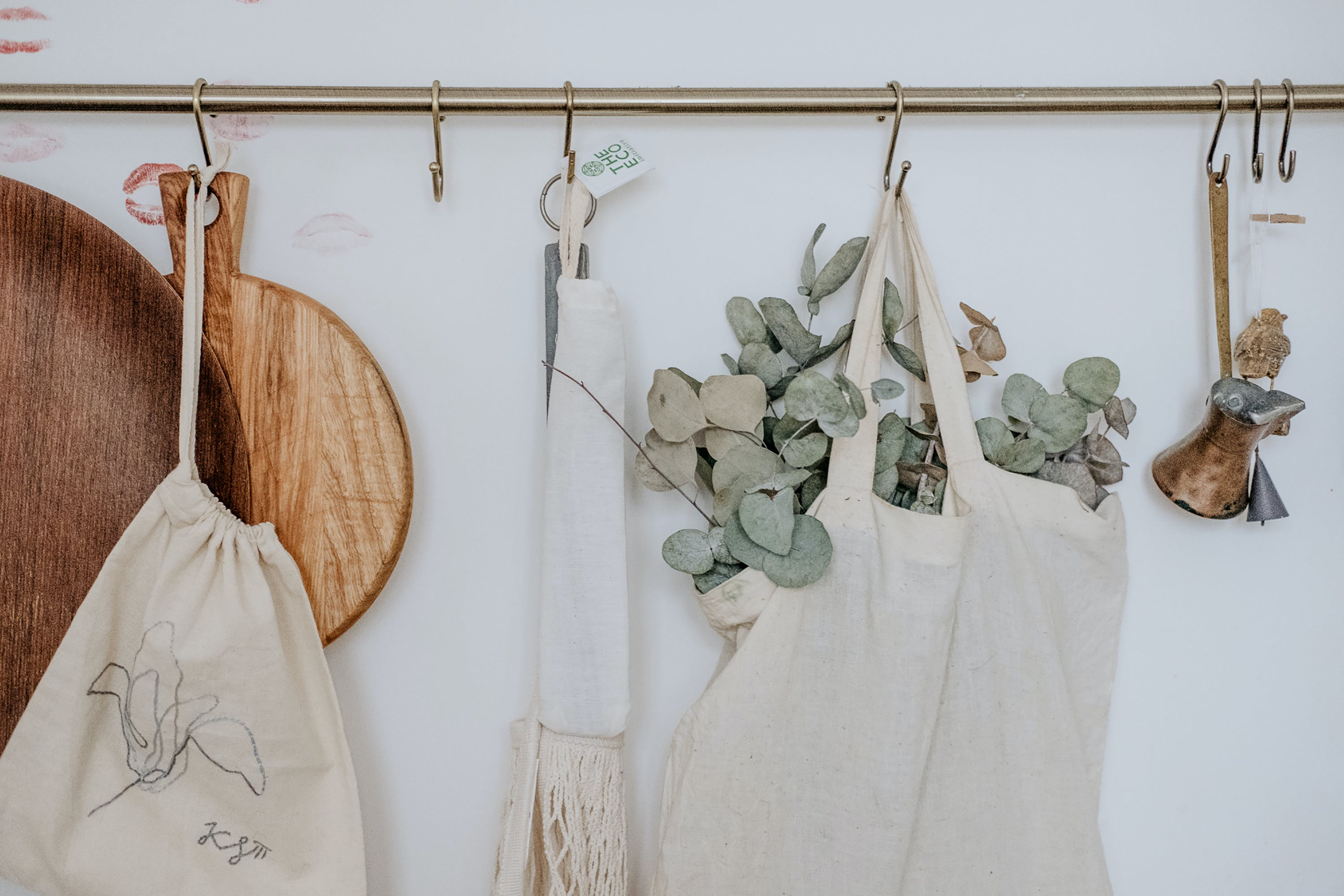 Aprons, Chopping Board and Bag Hanged on White Painted Wall