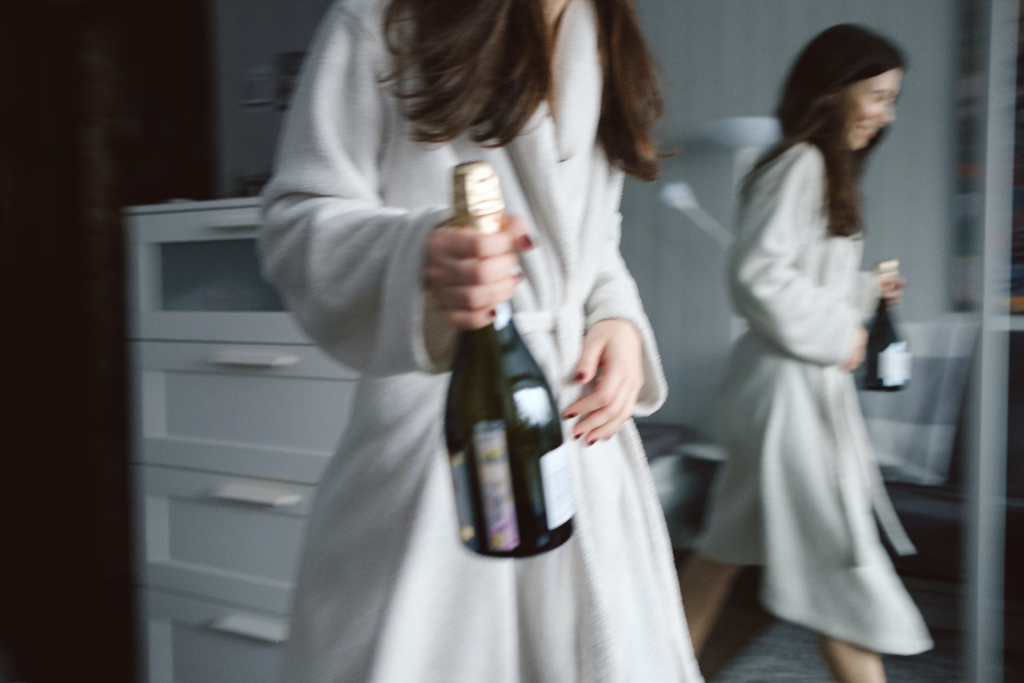 Photo of Woman in White Robe Carrying a Wine Bottle
