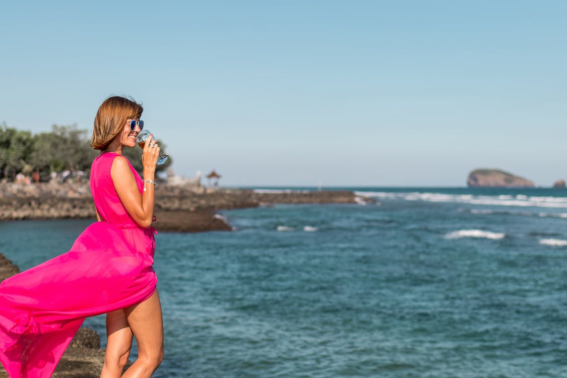 Woman Wearing Pink Dress Standing Near Ocean