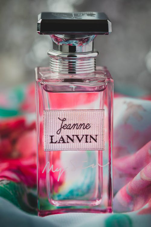 Transparent perfume bottle on vibrant fabric